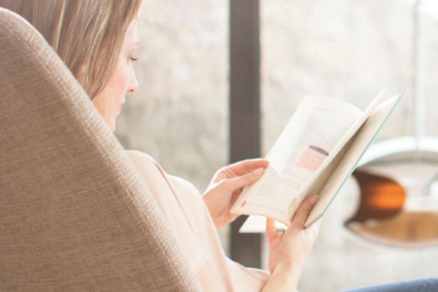 Woman reading amidst wellness tech.