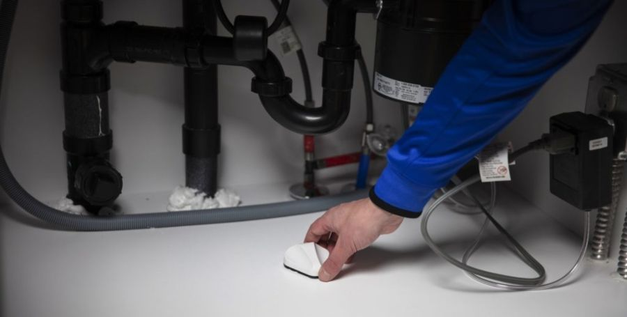 An environmental monitoring sensor being placed underneath a sink.