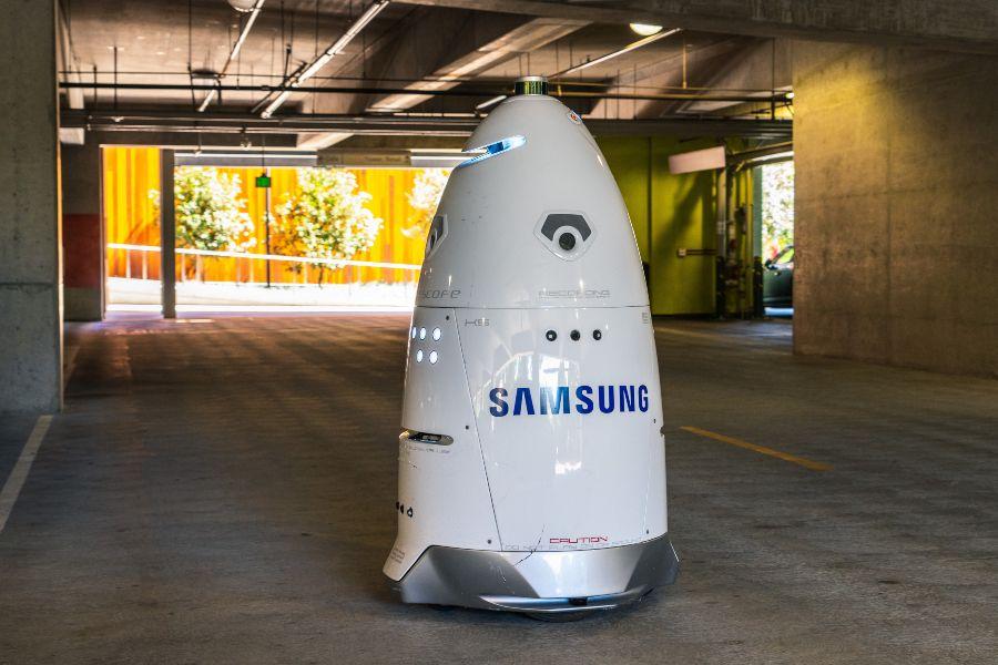 Security robot with Samsung Logo patrolling parking garage.