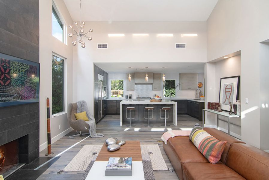 Scene of the remodeled living area and kitchen, which maximizes the natural light pouring into the room.