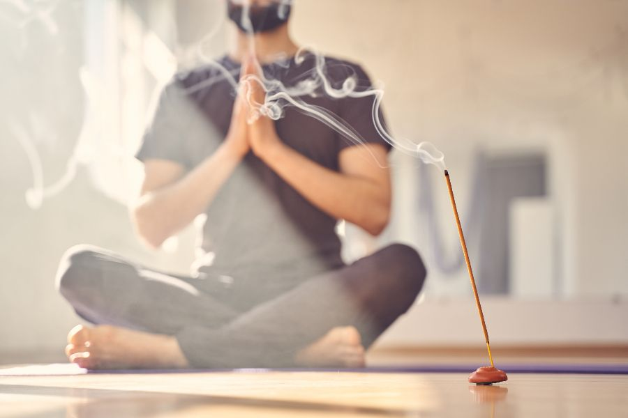 Man deepening his connection to yoga practices thanks to the power of scent from incense.